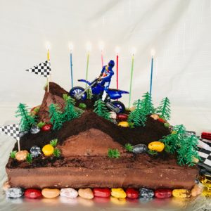 a motocross birthday cake with candles lit