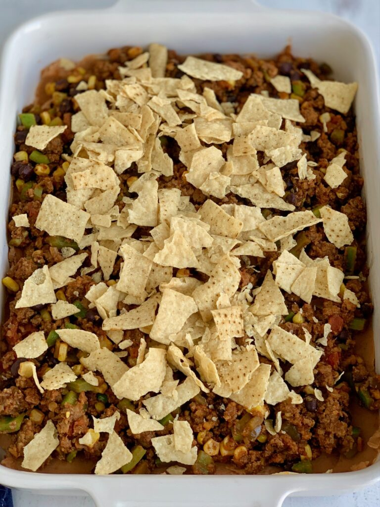 A baking dish filled with a layer of refried beans and taco meat sauce and crunched tortilla chips.
