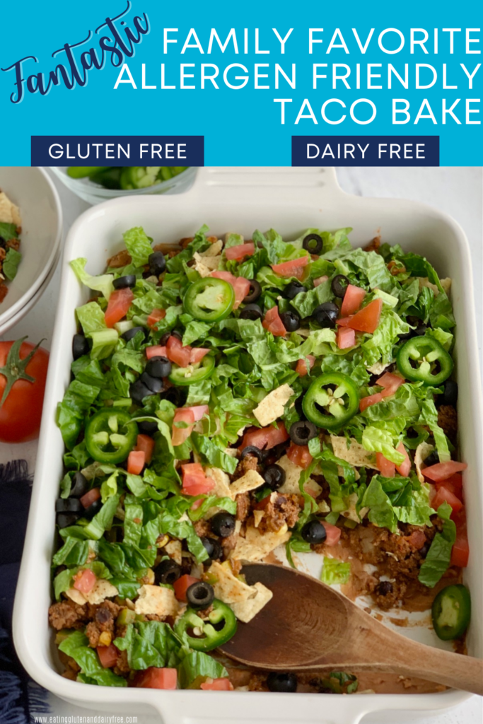 A baking dish filled with a layer of refried beans, taco meat sauce, crunched up chips, shredded romaine lettuce, diced tomatoes, jalapeno peppers, and black olives. Several scoops have been taken out.