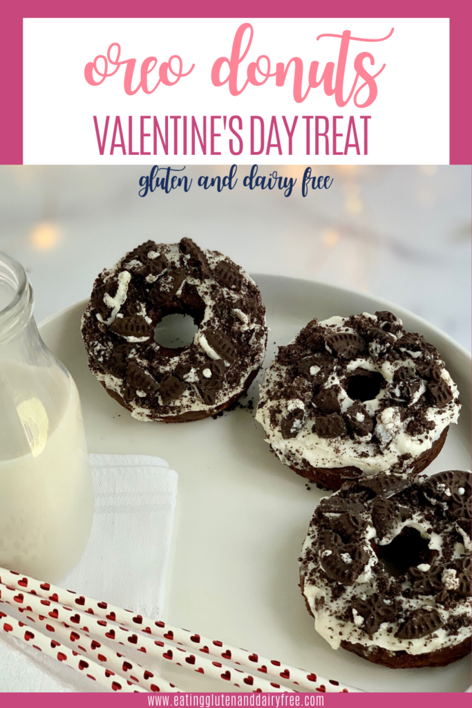 A white platter with three oreo donuts and a bottle of milk with valentine's day straws.