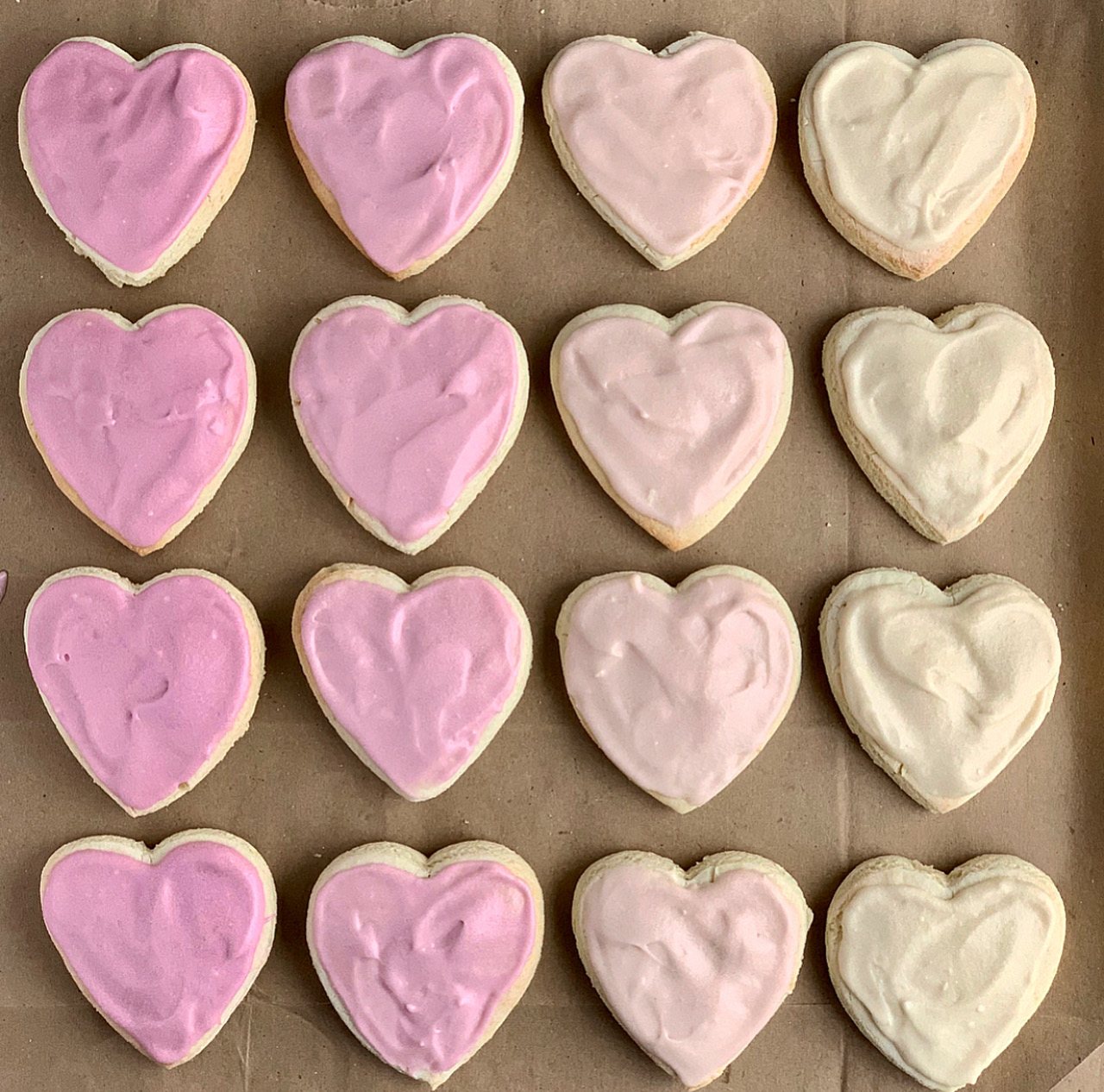 Several heart-shaped sugar cookies iced with an ombre coloring of pink to very light pink