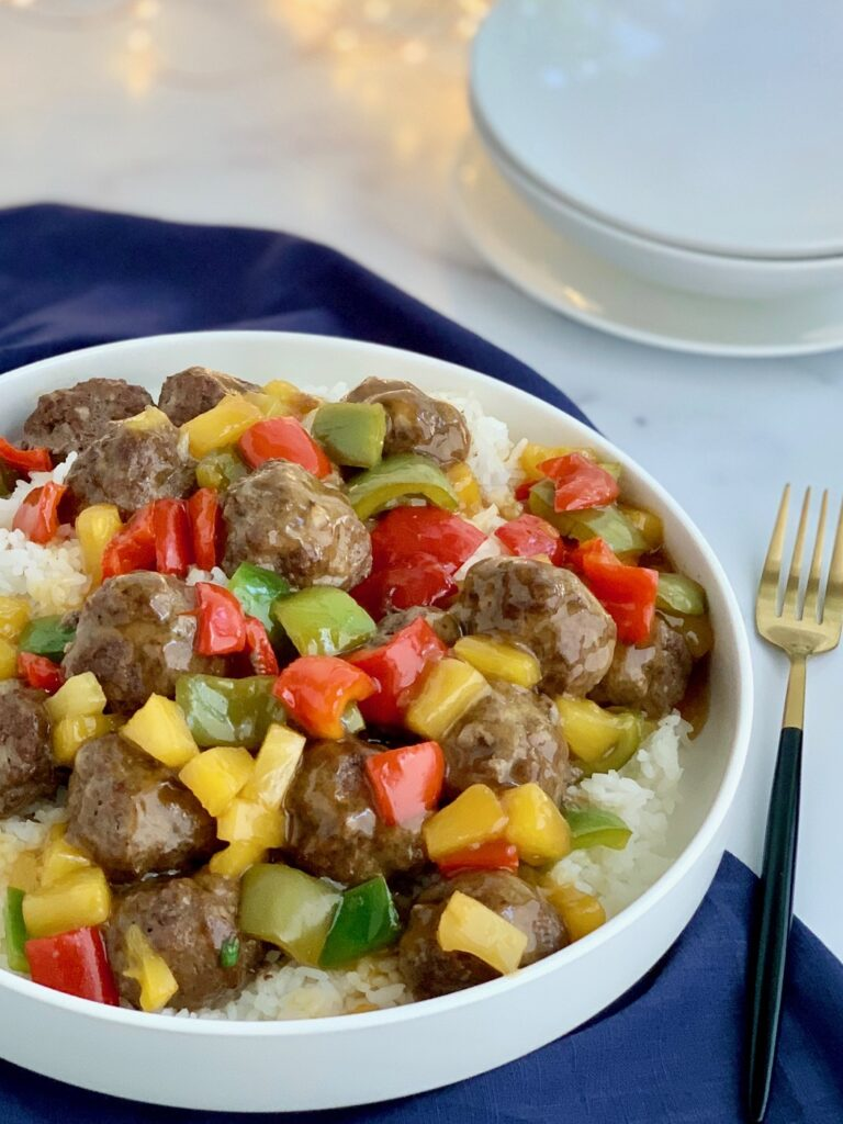 A white serving platter of steamed white rice with beef meatballs, pineapple chunks, and red, green and orange bell peppers.