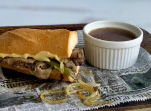Tender roast beef slices with sautéed onions and bell peppers with melted cheese layered between a sliced baguette next to a ramakin full of au jus.