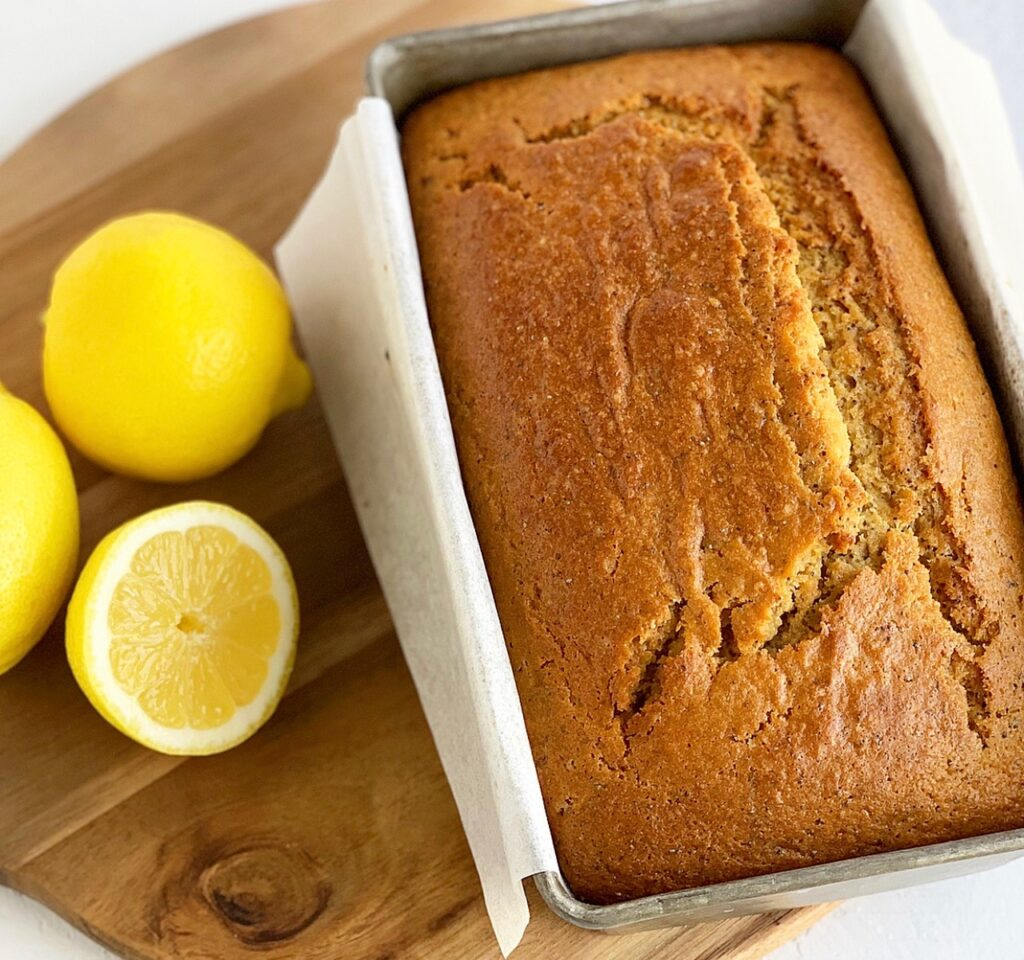 A baked loaf of Lemon Poppy Seed Bread in loaf pan next to three lemons.