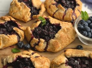 A flat pie dough with sides to keep a blueberry filling inside. With a garnish of fresh mint on top.