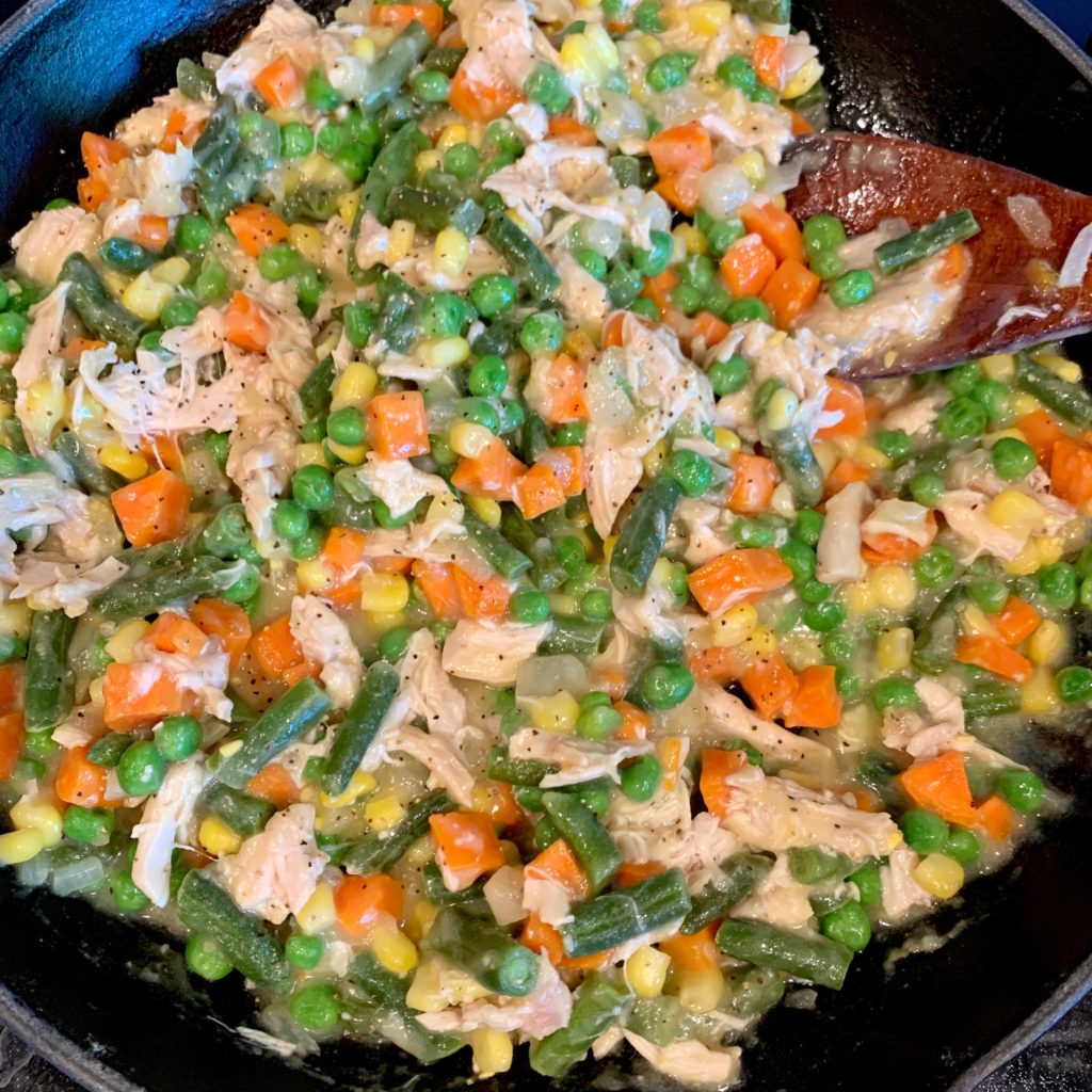 The thick chicken pot pie filling in a skillet with onions, chicken, carrots, corn, peas, and green beans.