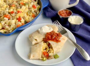 A white plate with 2 large breakfast burritos on it. One is cut open and you can see eggs, bell peppers, sausage, and hash browns. They are topped with dairy free sour cream and a dollop of salsa