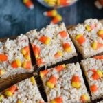 Rice krispie cereal with melted marshmallow over it and candy corns on top cut into large squares.