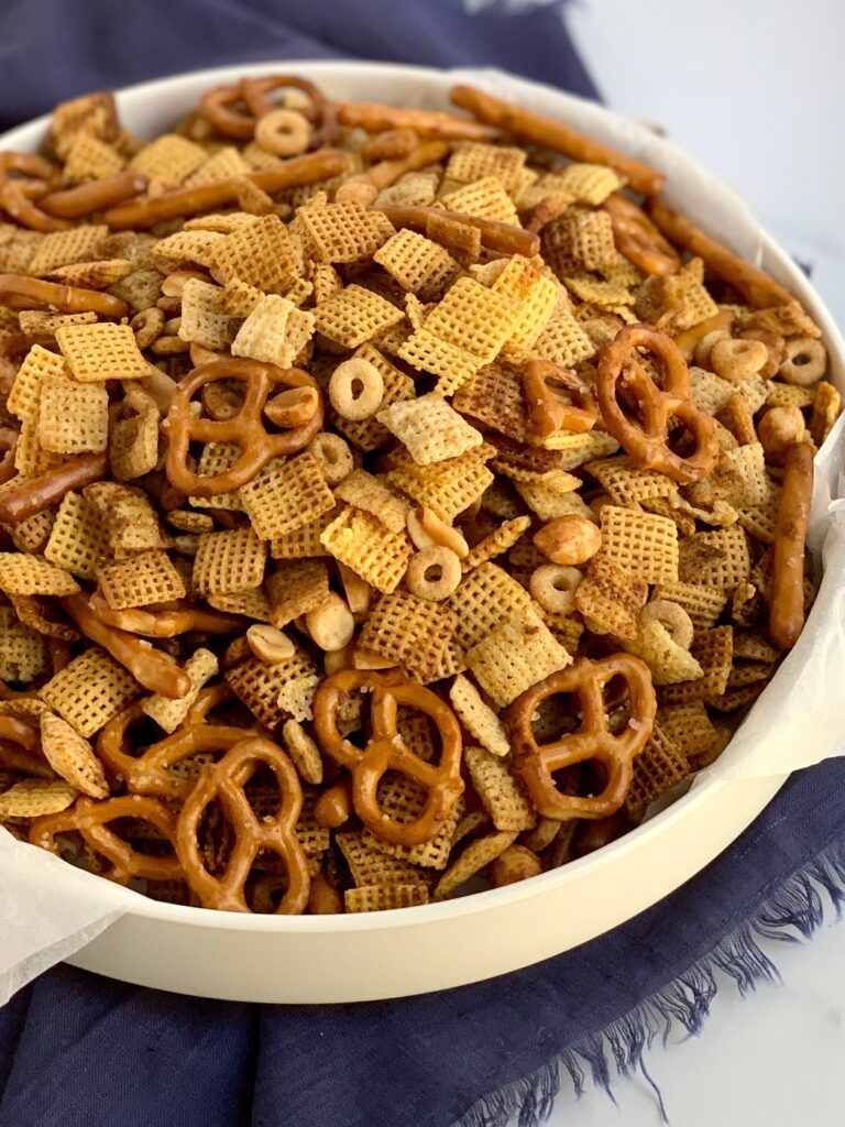 A large bowl of chex mix with pretzels, circle o cereal, chex mix, corn mix, and peanuts.