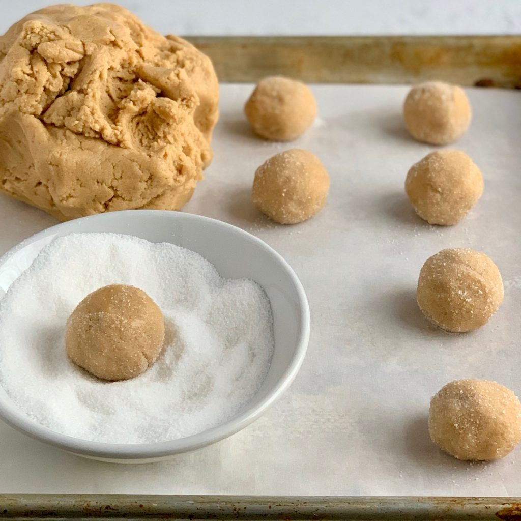A baking sheet with peanut butter cookies shaped in a ball an dipped in sugar before they go in the oven