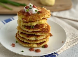 stack of mashed potato pancakes topped with dairy free sour cream, green onions, and bacon
