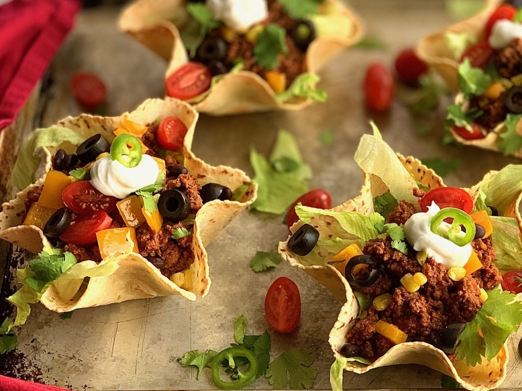 taco meat and toppings in a taco salad shell