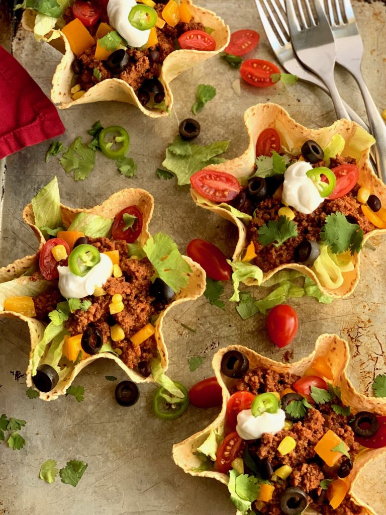 taco meat and toppings in a taco salad shell.