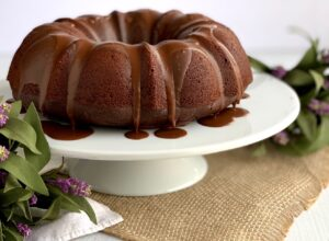 A chocolate bundt cake on a cake plate surrounded by spring flowers