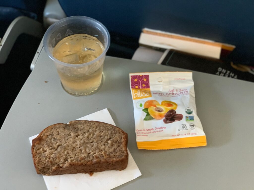 A slice of banana bread, and other snacks on an airplane tray table