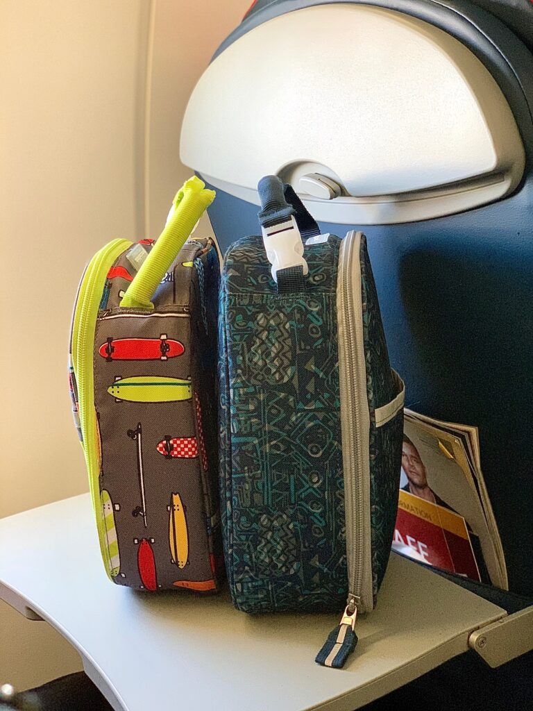 two food coolers sitting on an airplane tray table