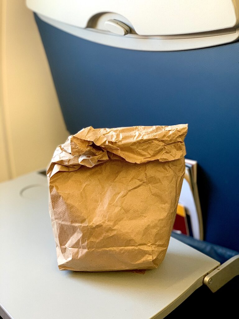 a brown bag on an airplane tray table