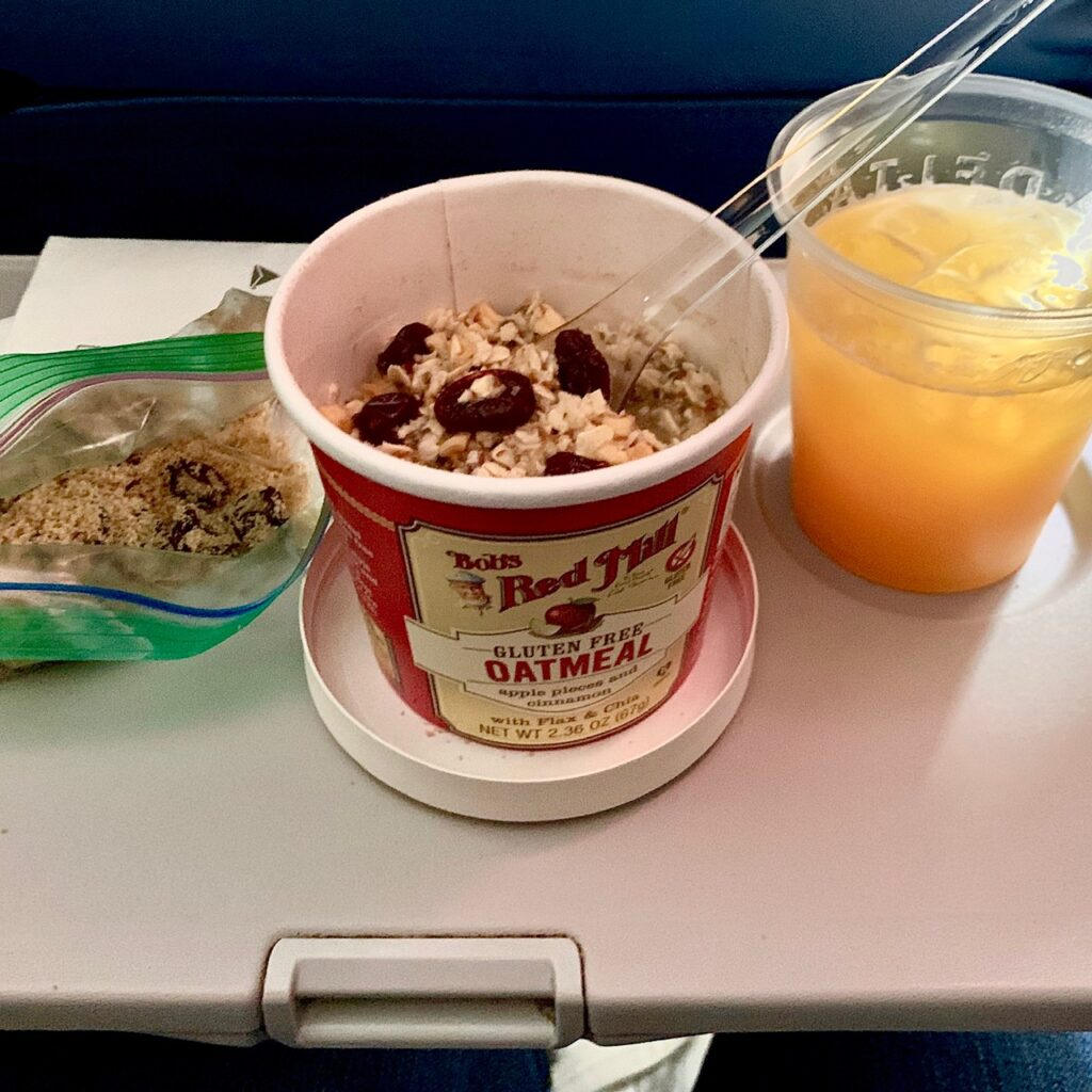 oatmeal and orange juice on an airplane tray table