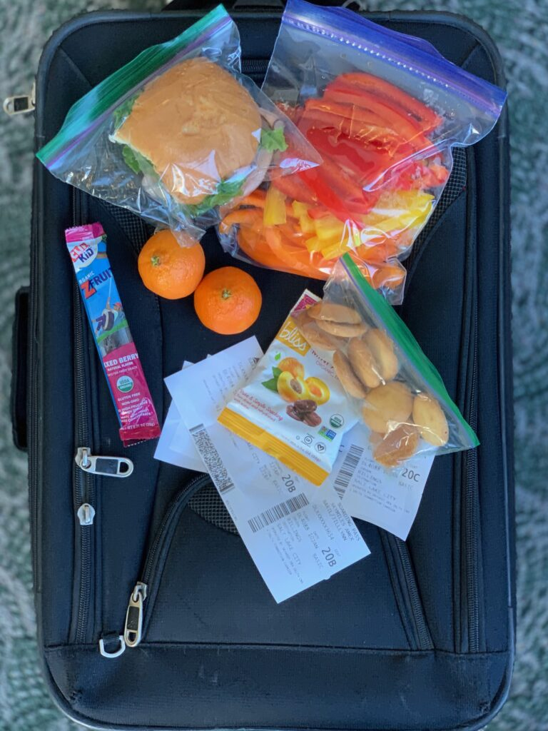 several snacks items on top of a carry on bag