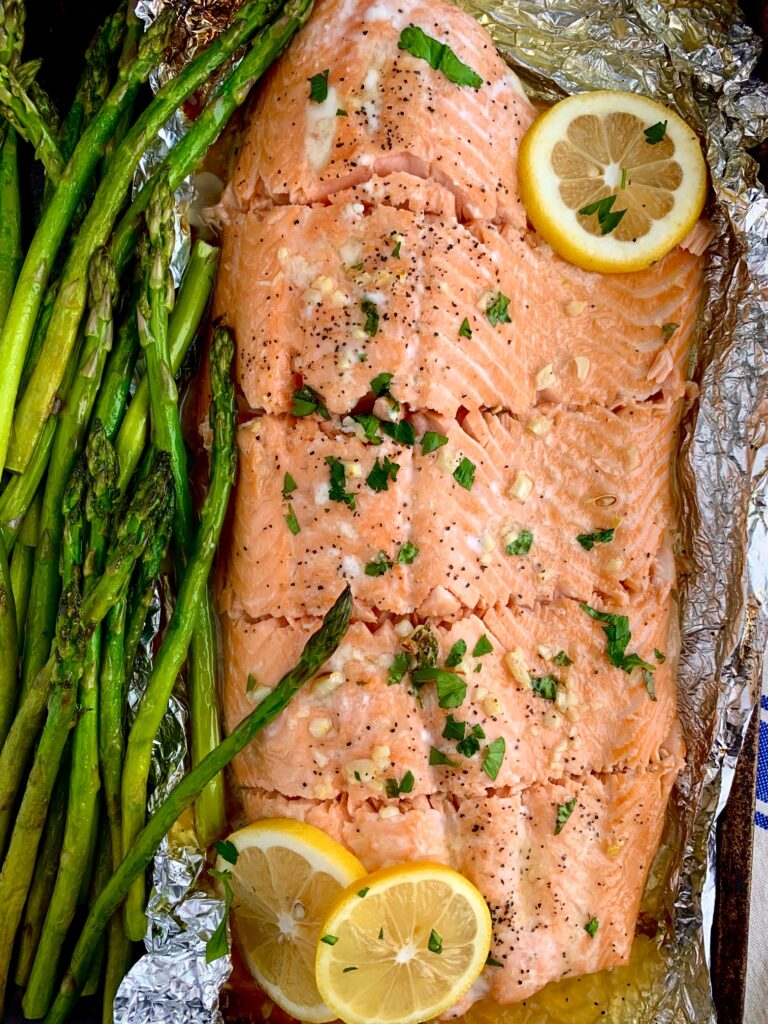 salmon in tin foil with lemon slices and asparagus