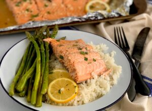 salmon on a be of rice with a side of asparagus