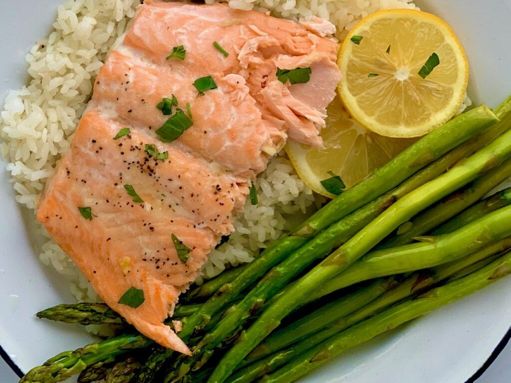 Flaky salmon on a bed of white rice with a side of asparagus.