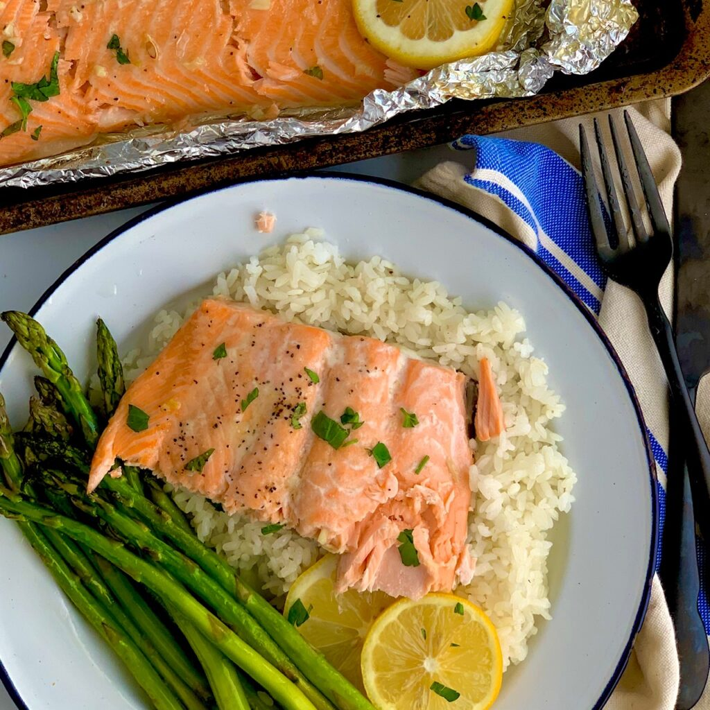 Flaky salmon on a bed of white rice and a side of asparagus.