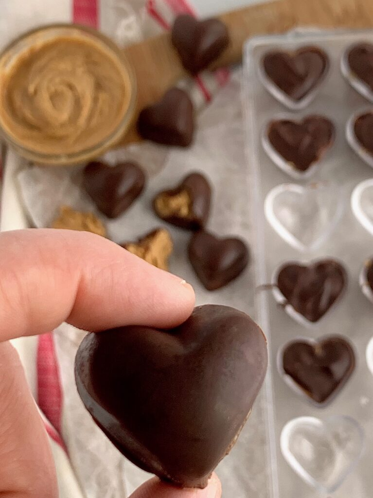 a hand holding a chocolate covered peanut butter heart