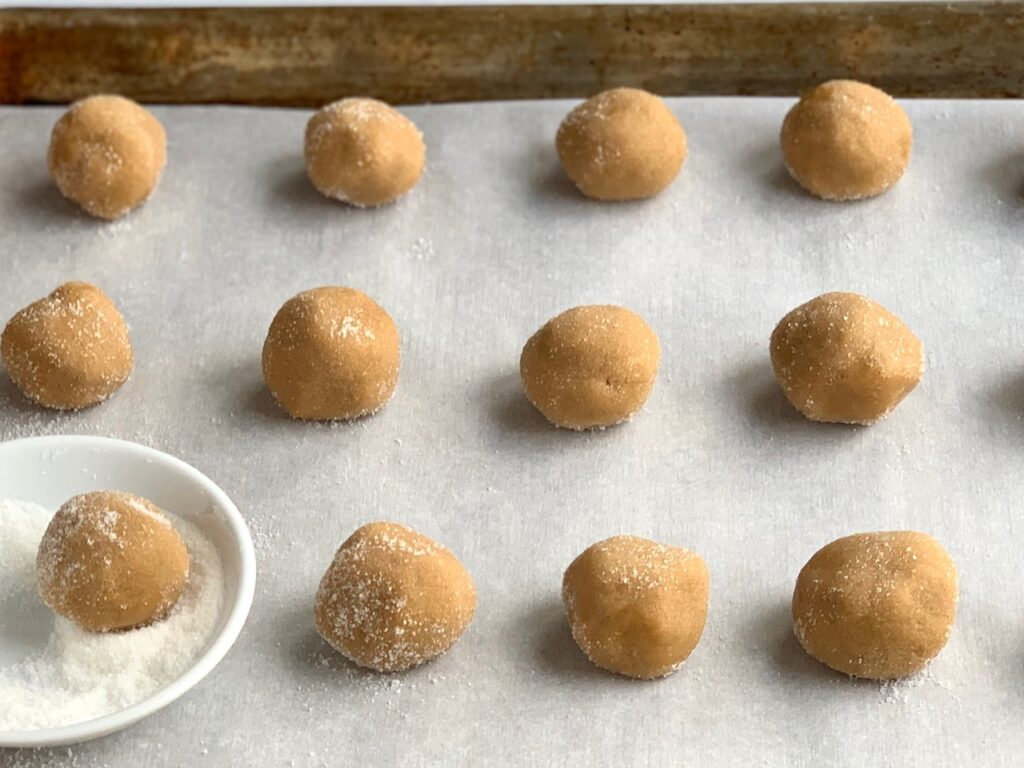 Peanut butter blossom dough rolled into balls with sugar