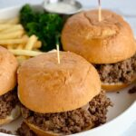 A white platter full of a meat mixture between hamburger buns with French fries.
