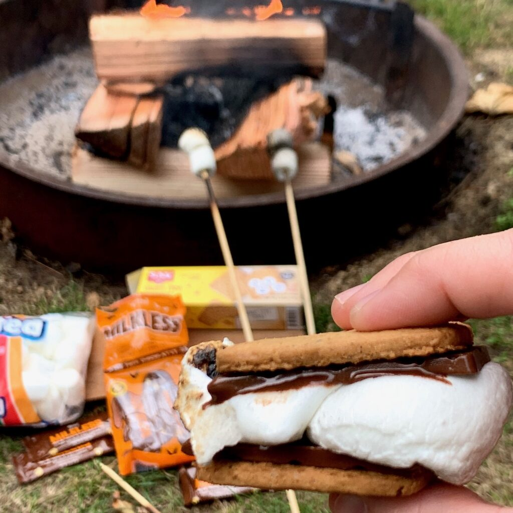 A s'more with melted chocolate oozing out by the campfire