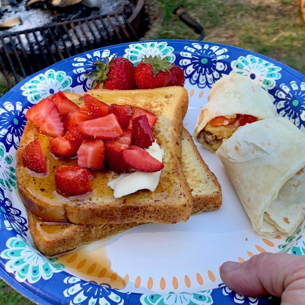 A plate with french toast, syrup, and sliced strawberries next to a breakfast burrito.