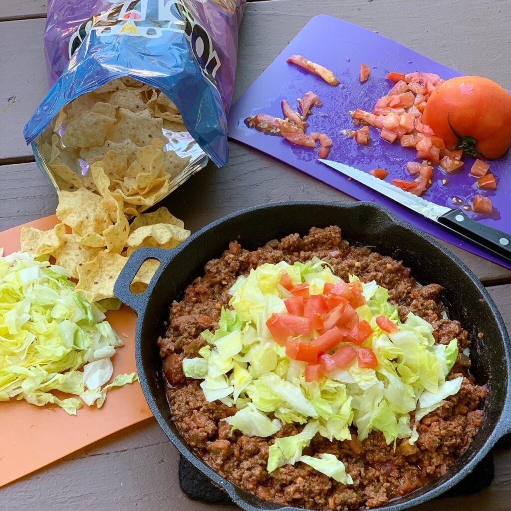A skillet filled with ingredients from the recipe an Easy Taco Skillet-- taco meat topped with chopped lettuce and diced tomatoes.