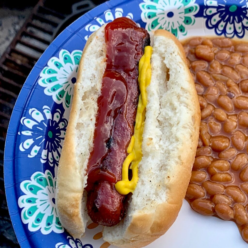 A grilled hot dog in a bun with ketchup and mustard. Baked beans on the side.