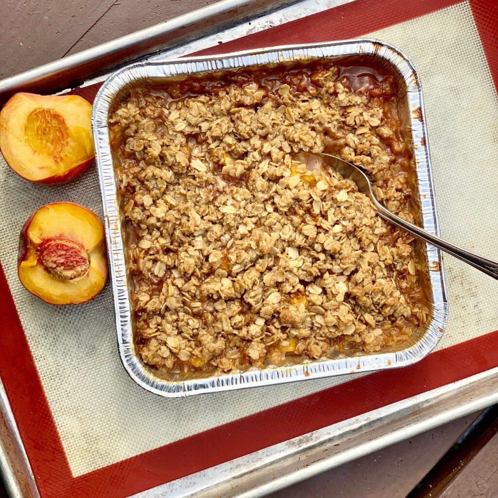 A fresh baked peach crisp on a picnic table