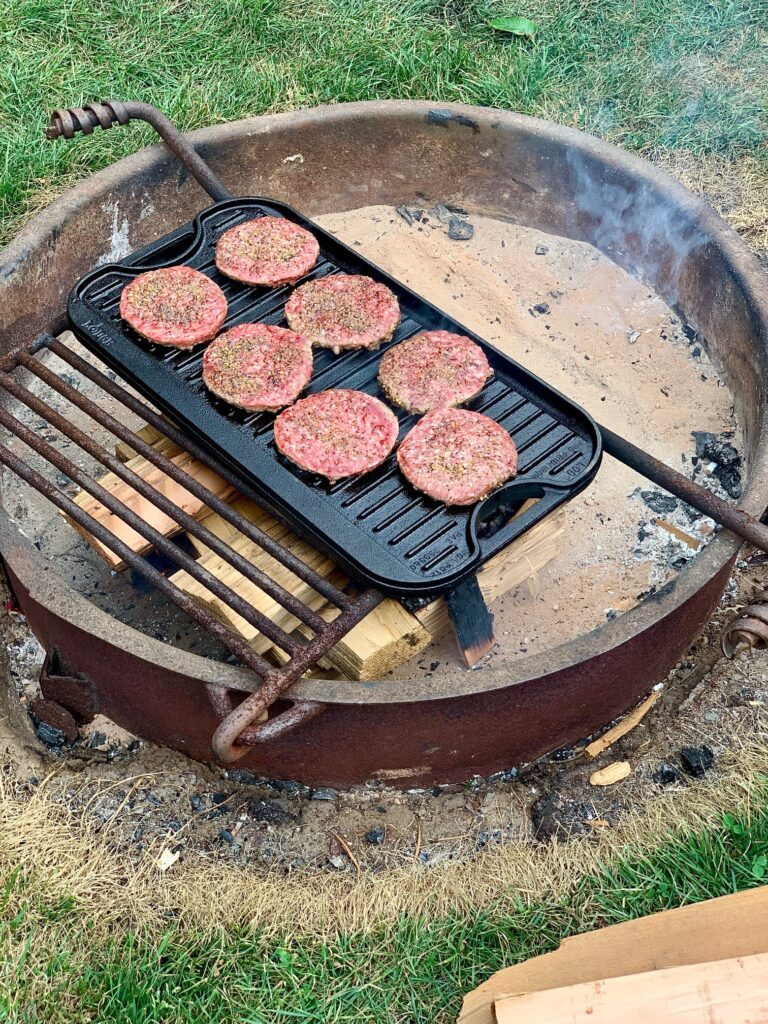 Hamburgers grilling over an open fame on a large cast iron griddle