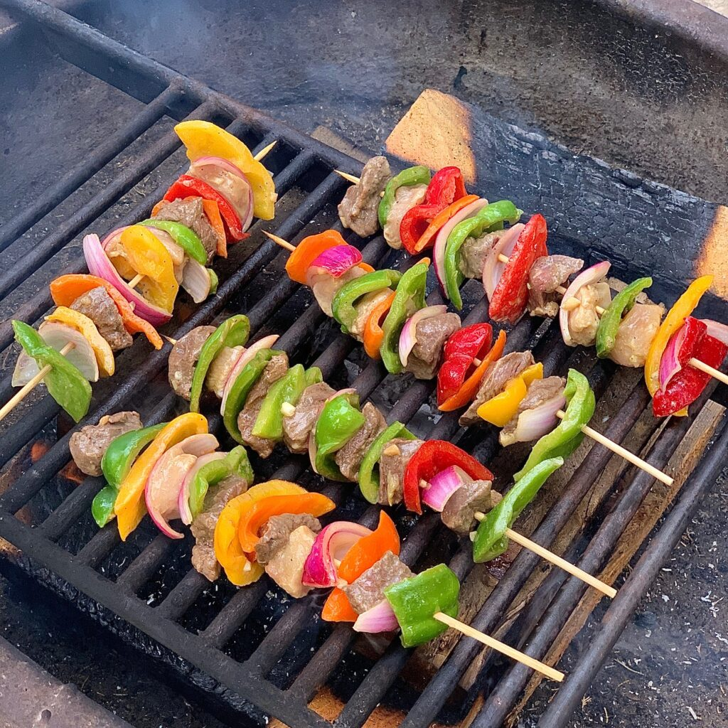 Colorful shish kabobs on wooden skewers grilling