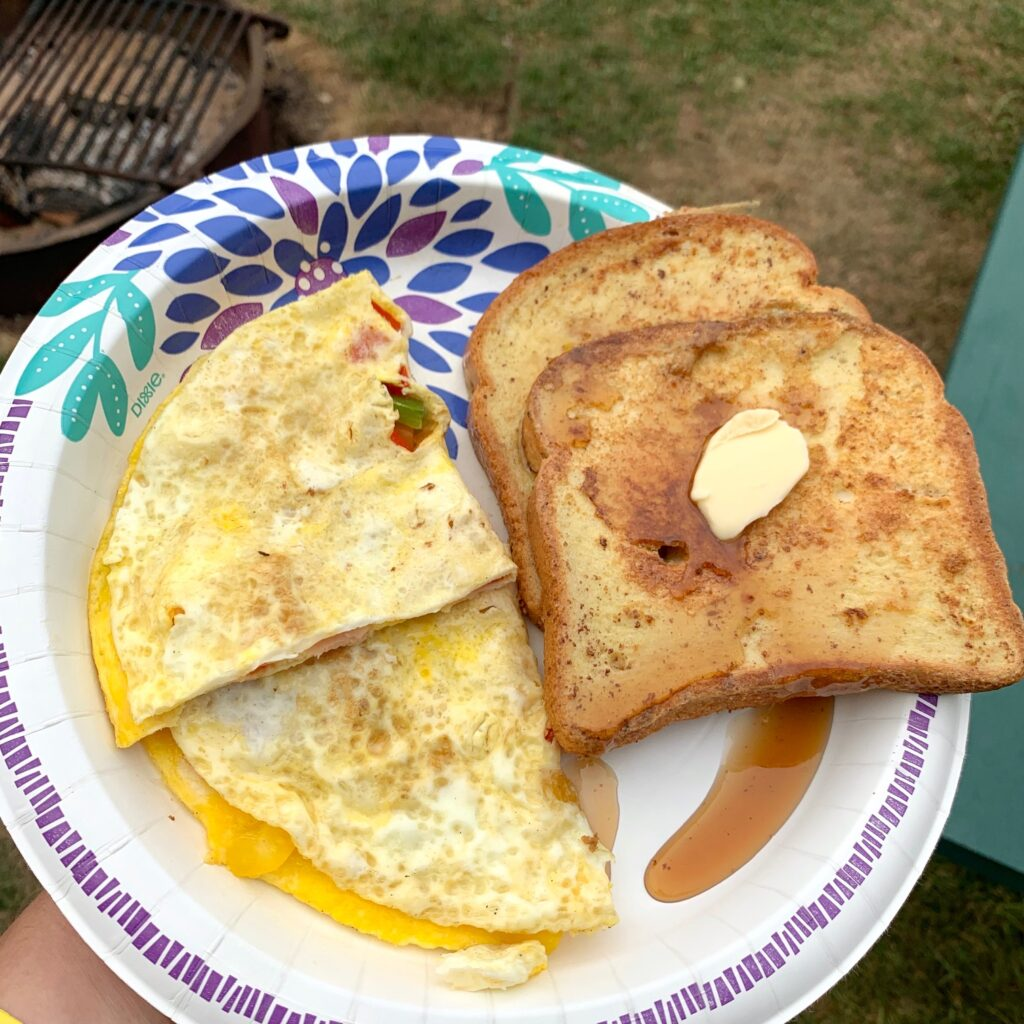 A plate with an omelet and two slices of french toast and syrup