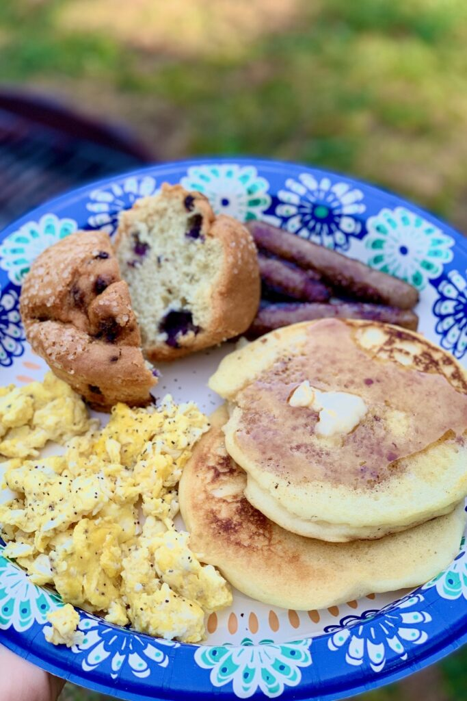 A plate full of allergen safe foods such as scrambled eggs, blueberry muffins, sausage links, and two pancakes smothered in maple syrup.