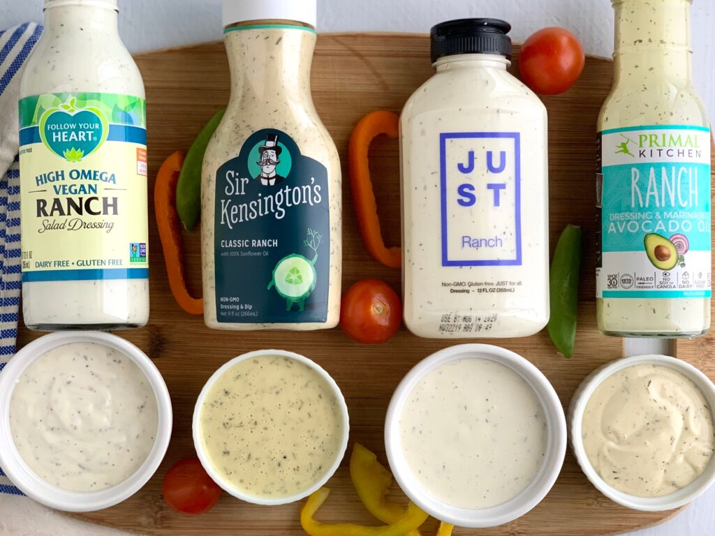 Four different dairy free bottles of ranch dressing laying down with a mini cup of dressing in front of each one to show what the dressing looks like.