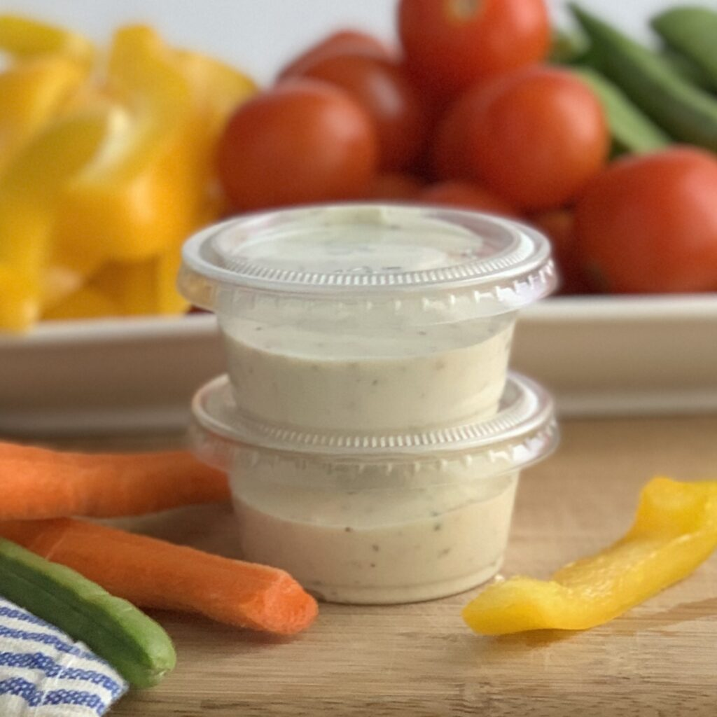 Two small plastic containers of dairy free ranch dressing.