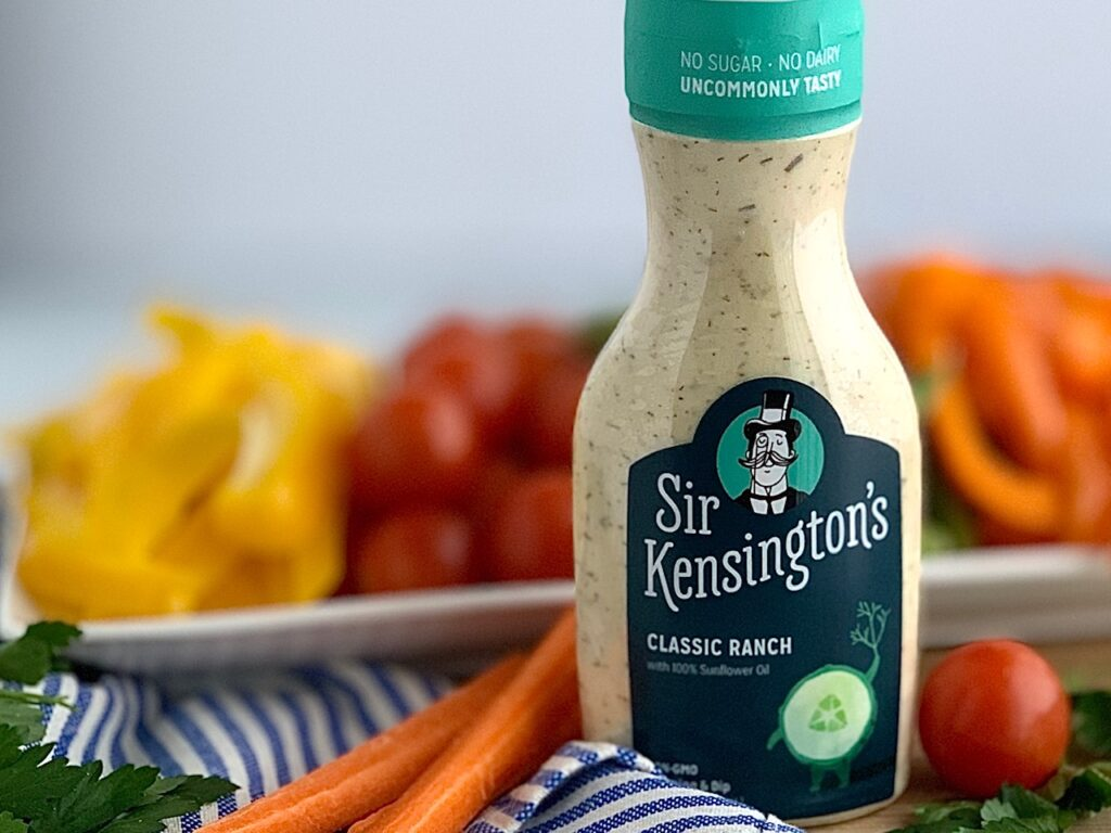 A bottle of Sir Kensington's Classic Ranch dressing next two carrots and a vegetable platter.