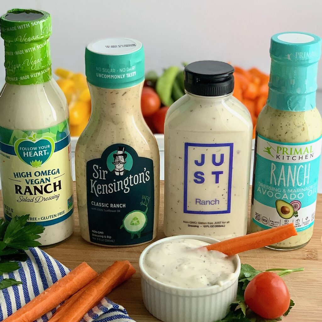 Four dairy free ranch dressings next to a small bowl of ranch dressing with carrots.