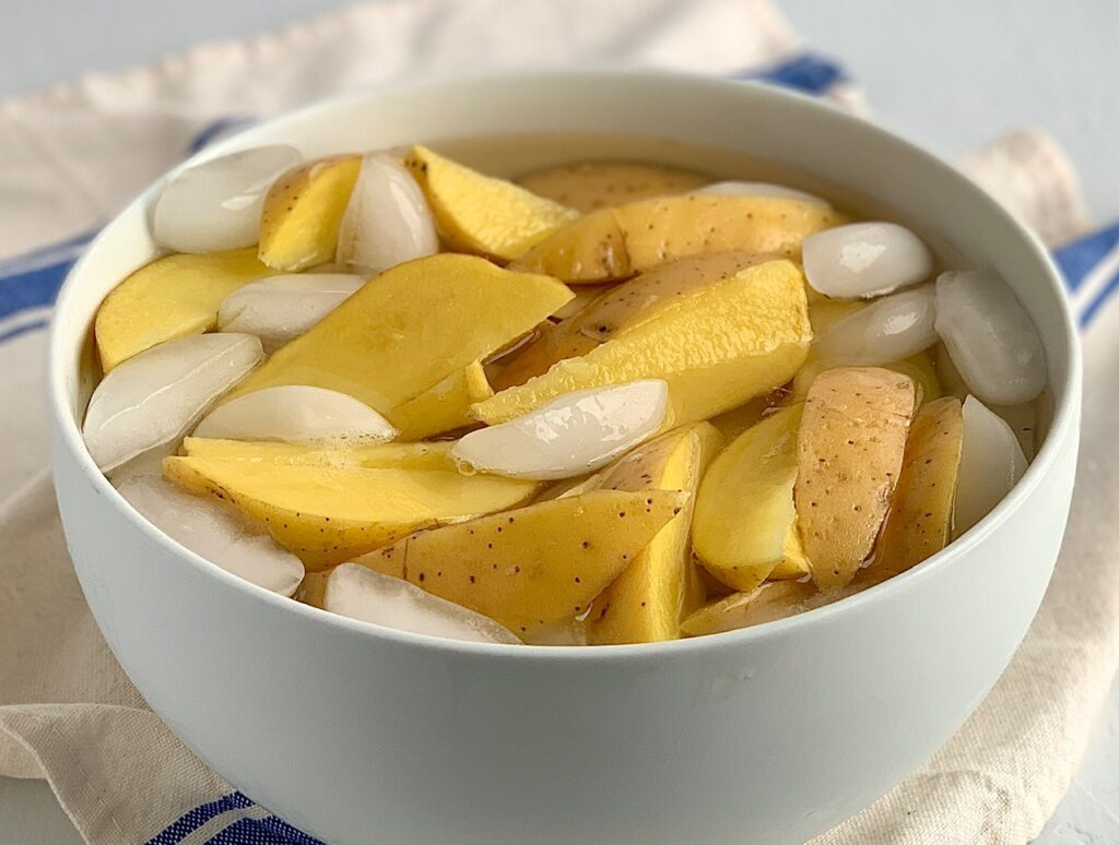 Potato wedges in a large bowl filled with ice water.