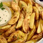 A plate heaping of baked potato wedges with dressing.