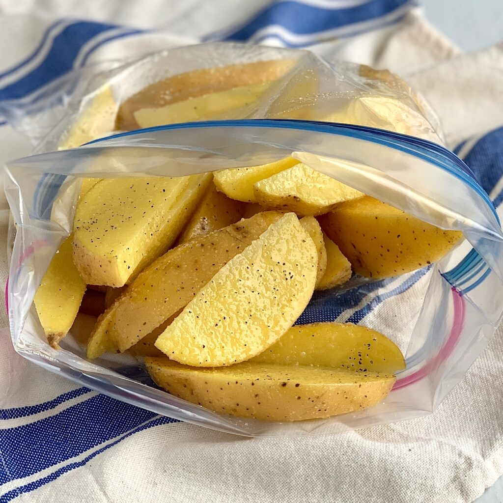 Potato wedges in a Ziploc bag with seasonings and oil