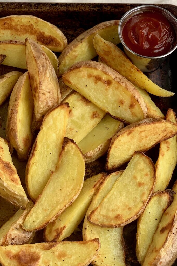 Baked potato wedges on a sheet pan with a container of ketchup