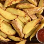 Baked potato wedges in a baking sheet with a container of ketchup