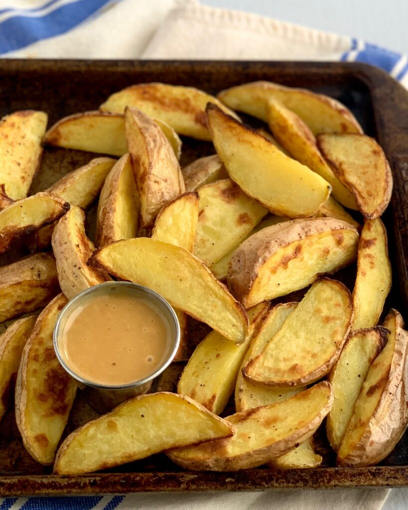 baked potato wedges on a baking sheet with a small container of Copycat Chick-Fil-A Sauce