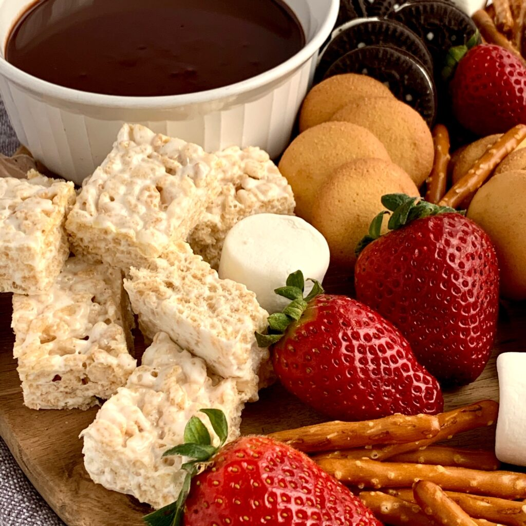 A dessert platter with strawberries, mini brownie bites, pretzel rods, oreo sandwich cookies, marshmallows, mini rice krispie treats and ganache dipping sauce.